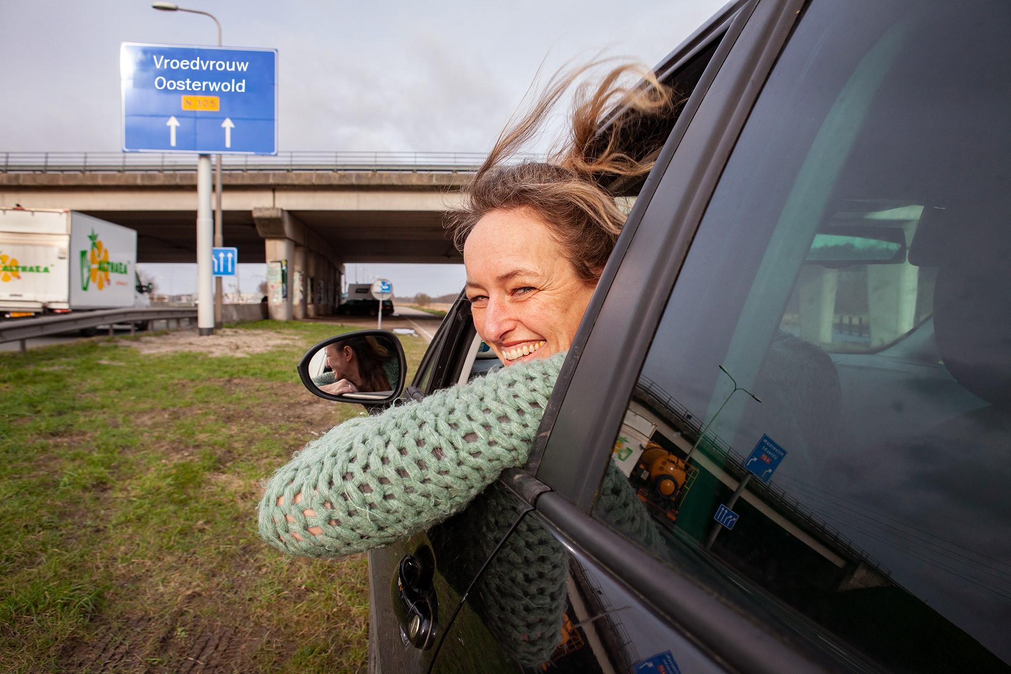 Michelle in haar auto, kijkend uit raampje, op achtergrond richtingbord met 'vroedvrouw oosterwold'