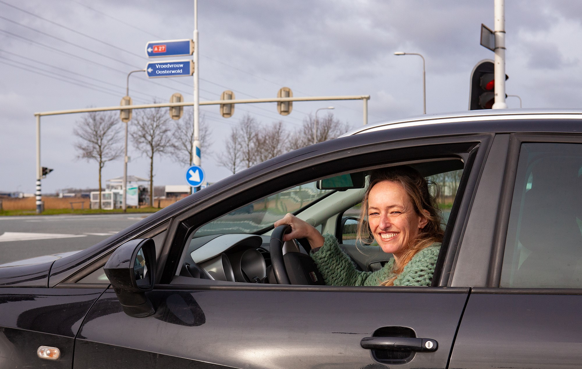 Michelle achter het stuur van haar auto rijdend in de richting van 'vroedvrouw oosterwold'